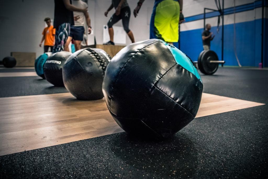 Ein schwarzer Medizinball liegt auf der schwarzen gummierten Seite eines Gewichtheber Bodens. Im Hintergrund sind weitere Medizinbälle sowie trainierende Personen und eine Langhantel mit Gewichten zu erkennen.