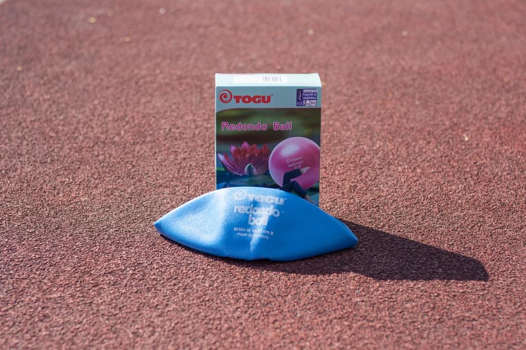 Ein blauer Pilates Ball liegt nicht aufgepumpt auf einer roten Tartanbahn. Dahinter steht die Hersteller Verpackung, worauf ein rosa Pilates Ball zu erkennen ist.