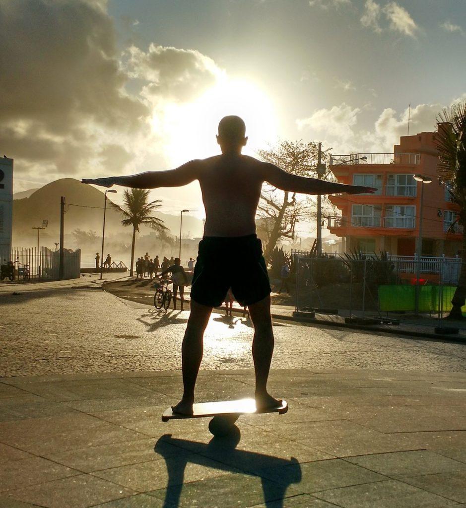 Ein Mann steht auf einem Balance Board und wird von hinten durch die Sonne angestrahlt, sodass man nur die Umrisse erkennen kann. Im Hintergrund sind zudem noch eine Straße, Menschen und Häuser zu erkennen.