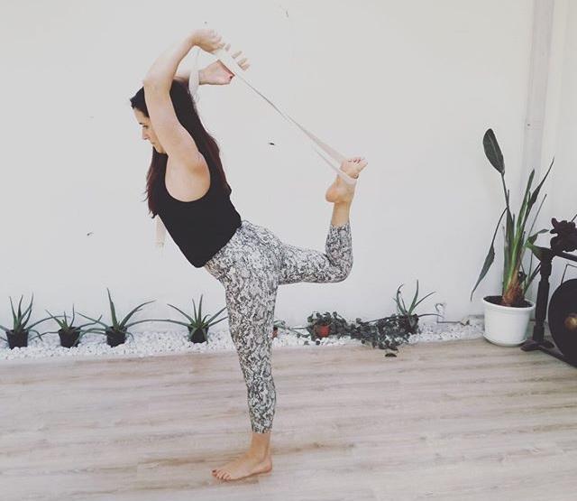 Eine Frau steht auf einem Bein und dehnt ihr anderes Bein mit der Hilfe eines Yoga Gurtes hinter dem Rücken. Im Hintergrund sind Pflanzen an der Wand aufgereiht.